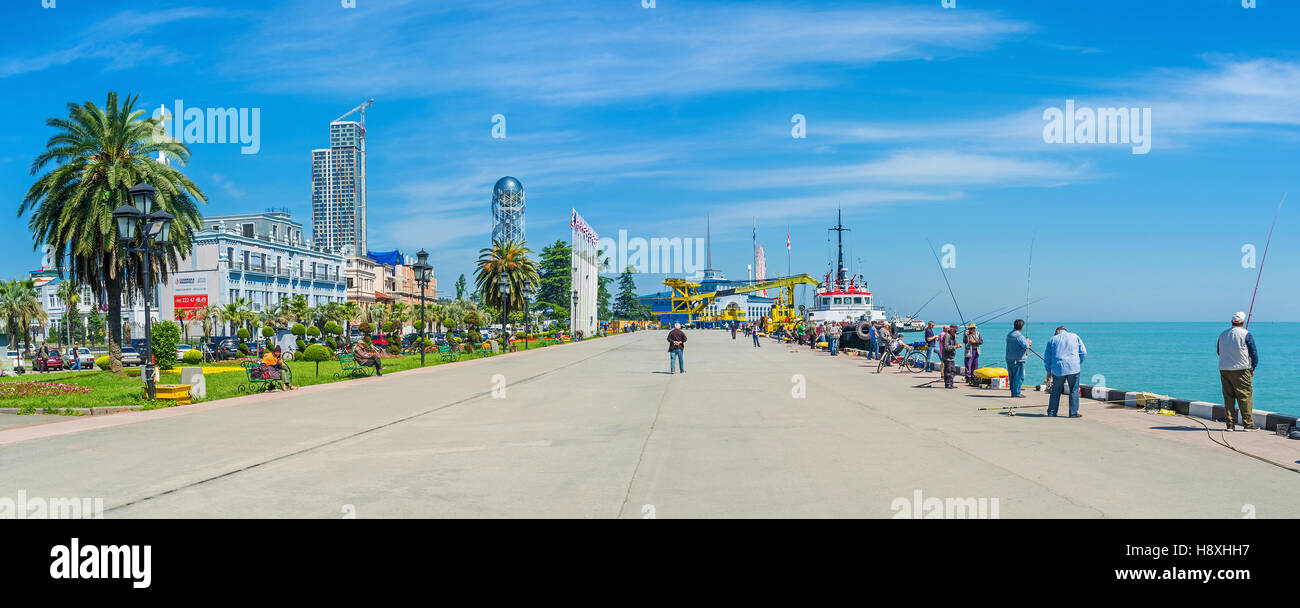 The seaside promenade with beautiful ornamental garden, moored longboats and many fishermen - Stock Image