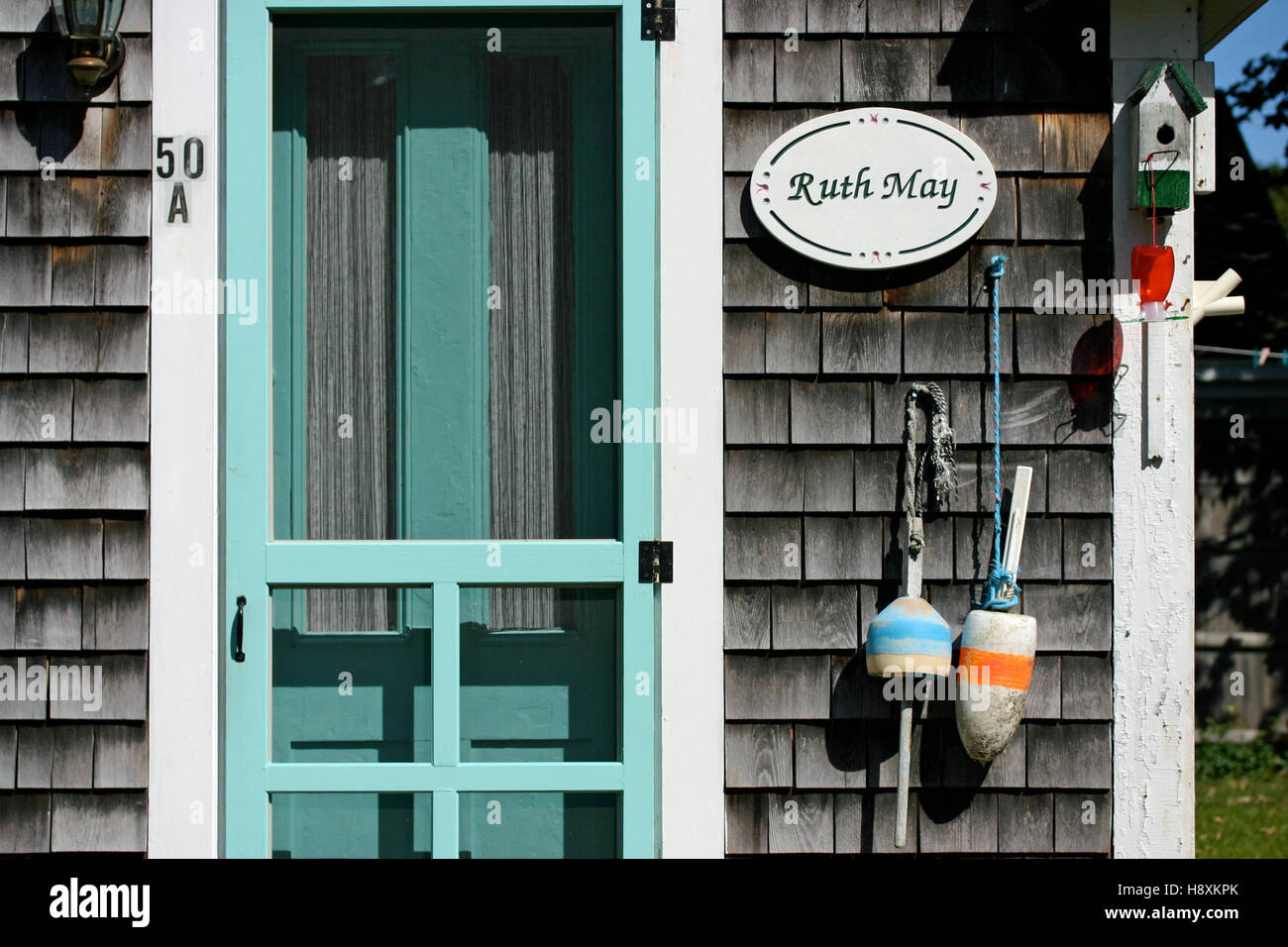 Close-up of a Cape Cod vacation cottage with aqua colored door and gray weathered shingles Stock Photo