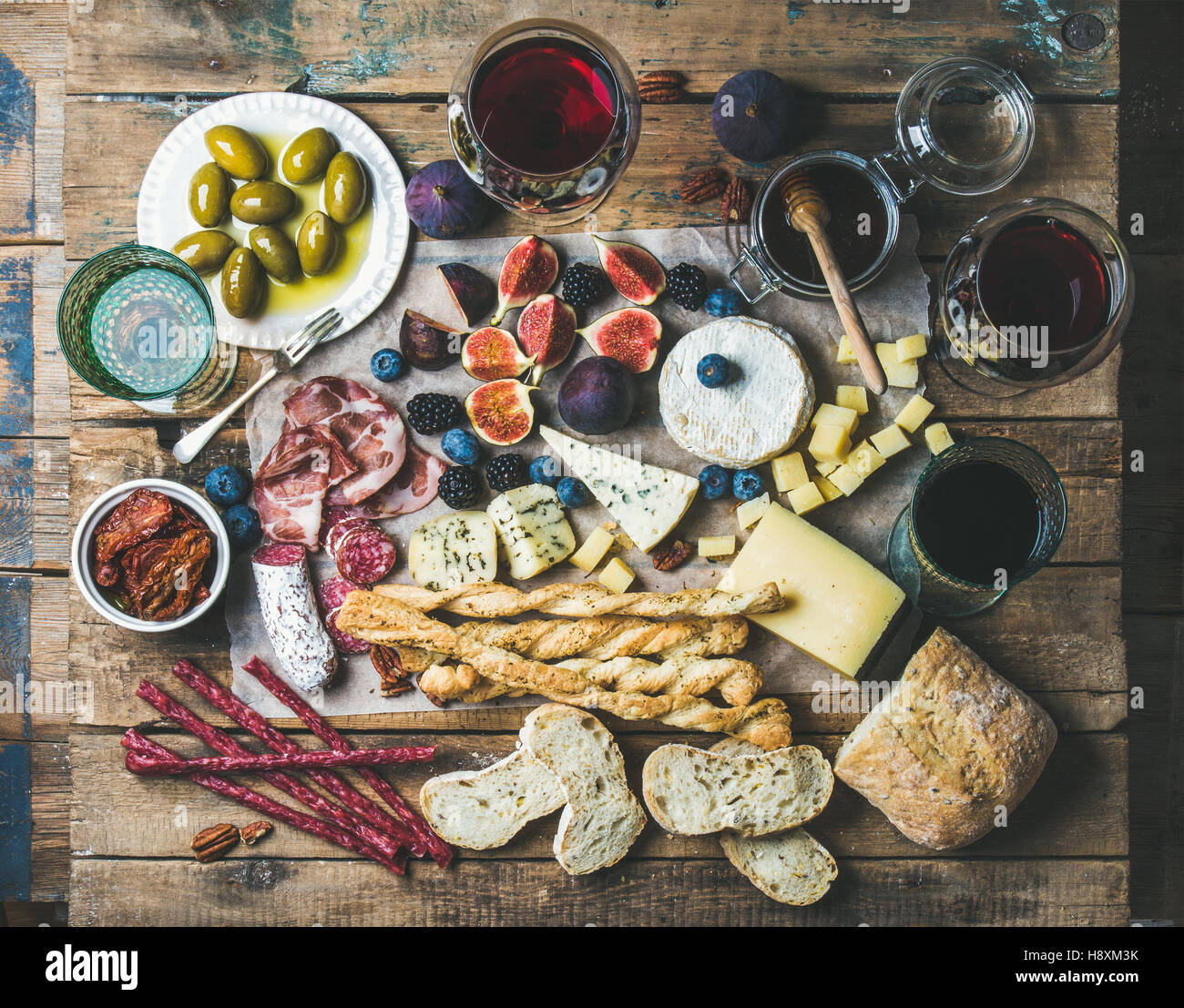 Wine and snack set with wines, meat, bread, olives, fruits - Stock Image