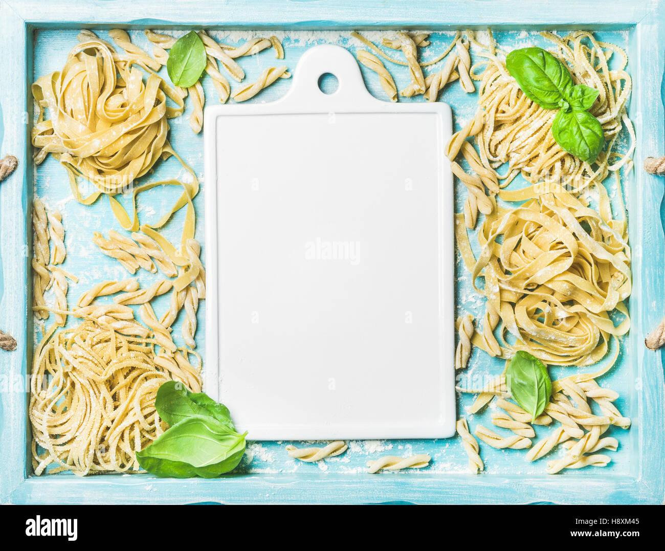 Various homemade fresh uncooked Italian pasta and white ceramic board Stock Photo