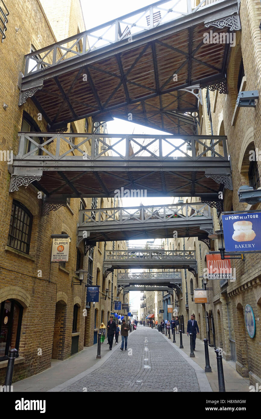 View along Shad Thames looking up at the overhead walkways between warehouse apartments of Butlers Wharf - Stock Image