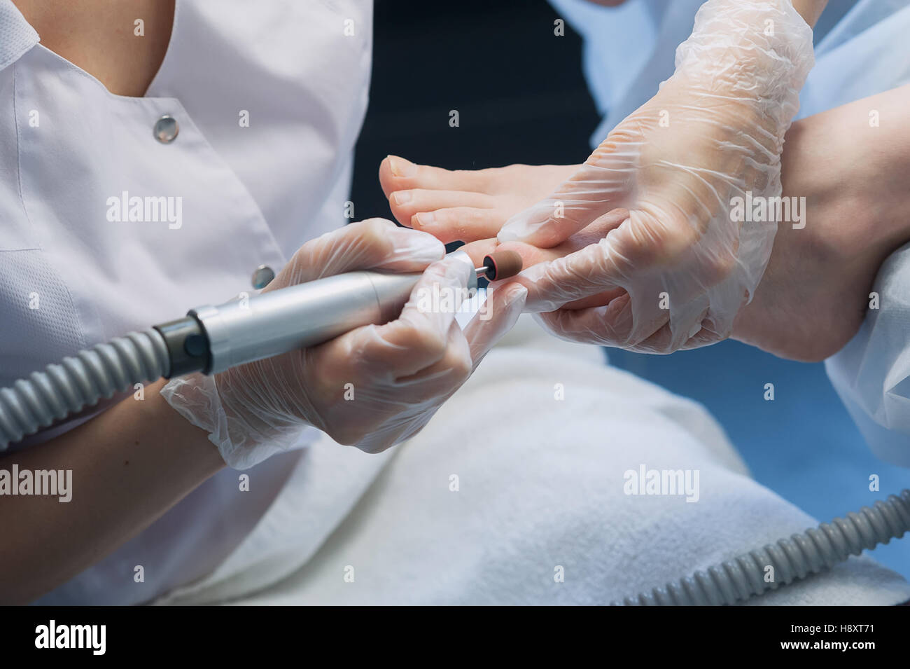 profesional nail technician sanding nails with machine - Stock Image