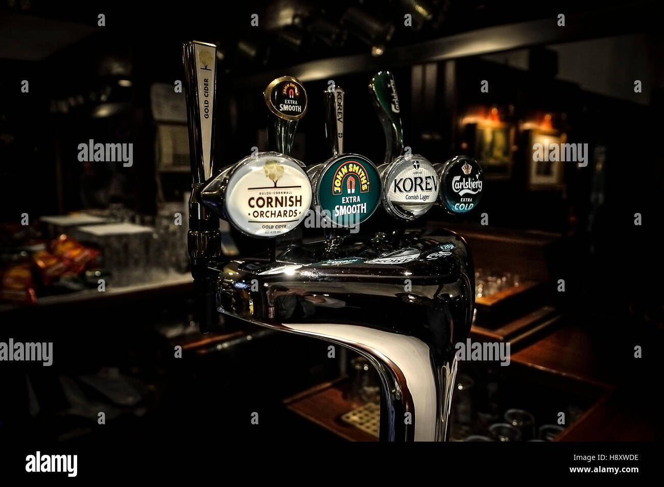 Illuminated beer, lager and cider pumps in a bar. - Stock Image