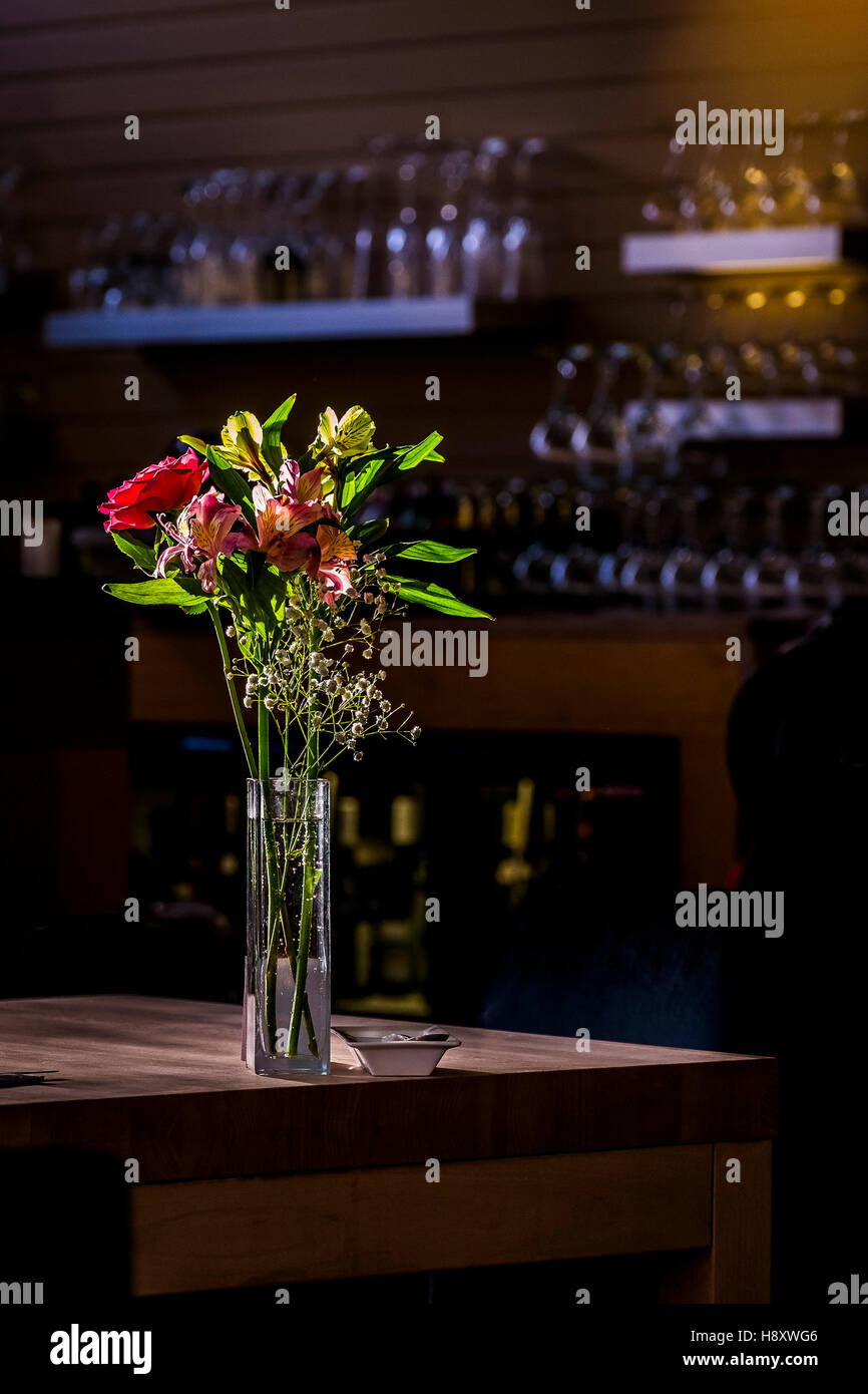 A vase of flowers on a restaurant table. - Stock Image