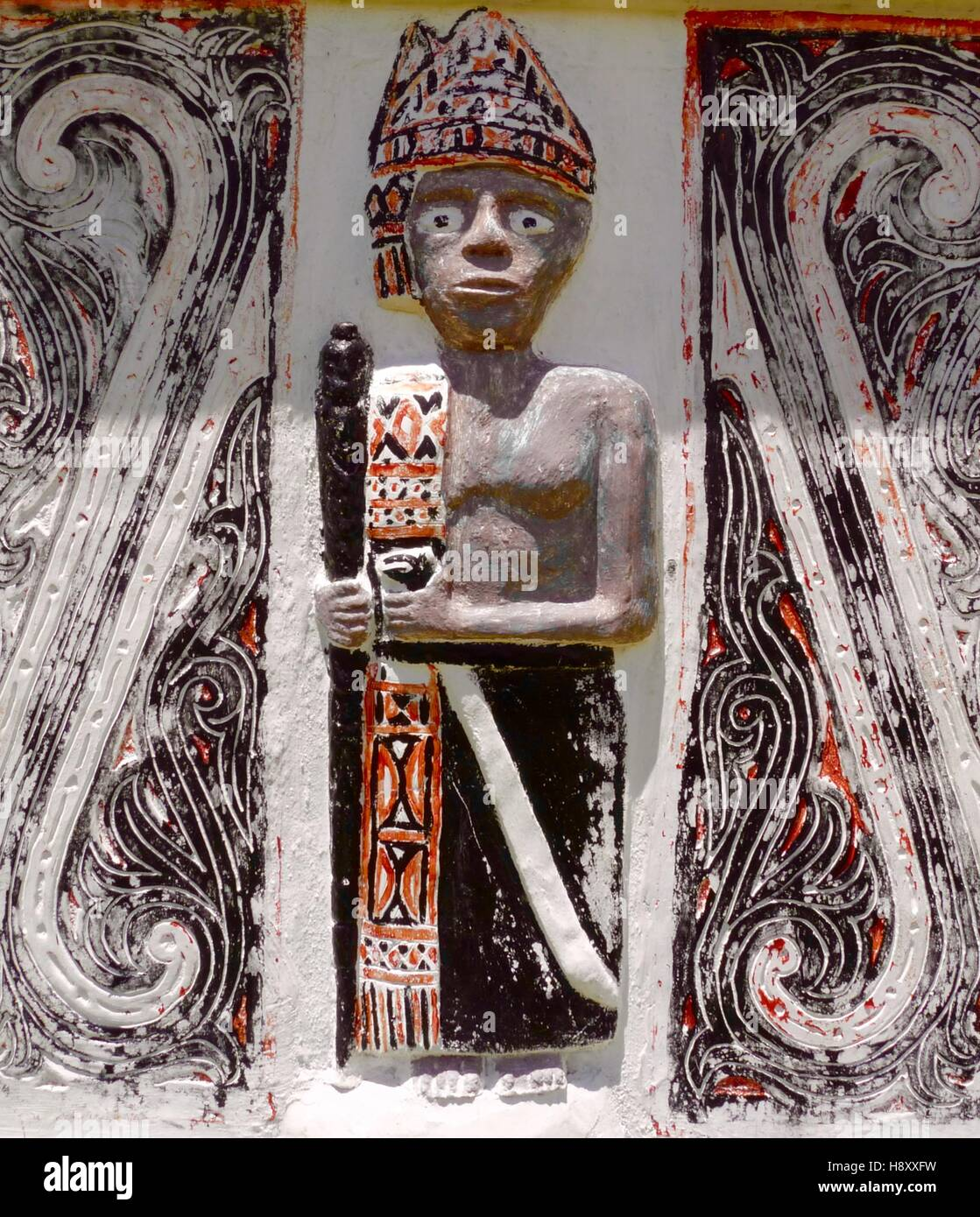 Carving of figure of Batak hunter with traditional colours and design of that ethnic group from the Indonesian island - Stock Image
