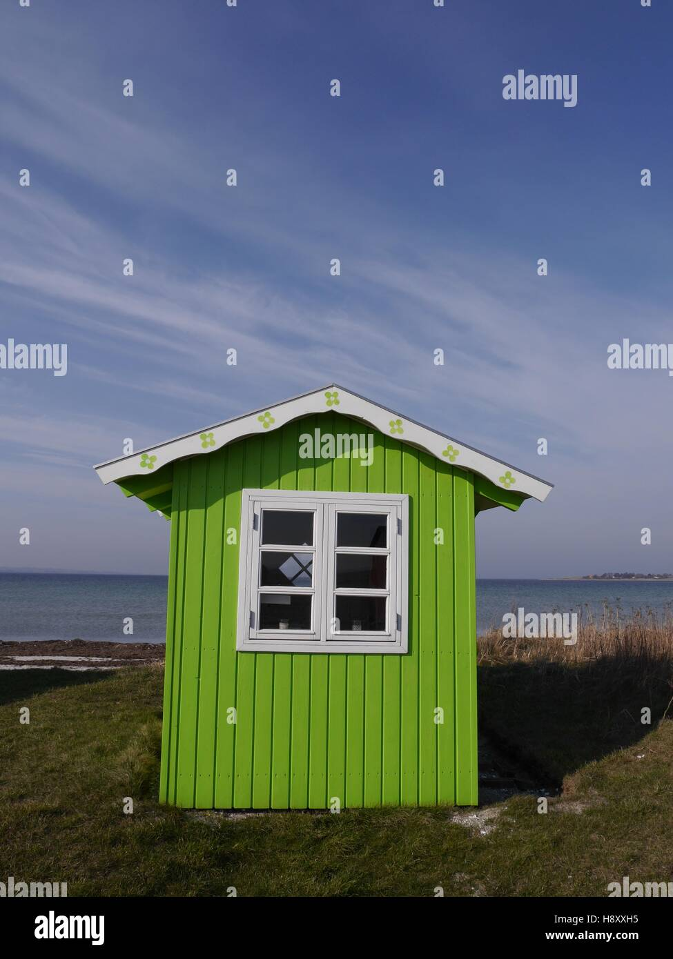 A cute lime-green beach hut with white roof and window frame against a background of blue sea and blue sky. - Stock Image