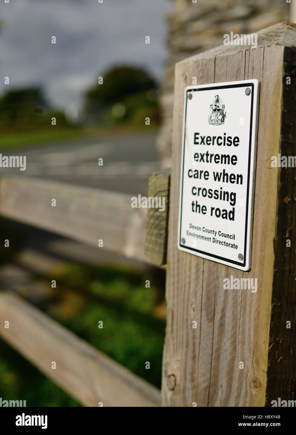 Warning notice on a gatepost where the South West Coast Path emerges onto a road. - Stock Image