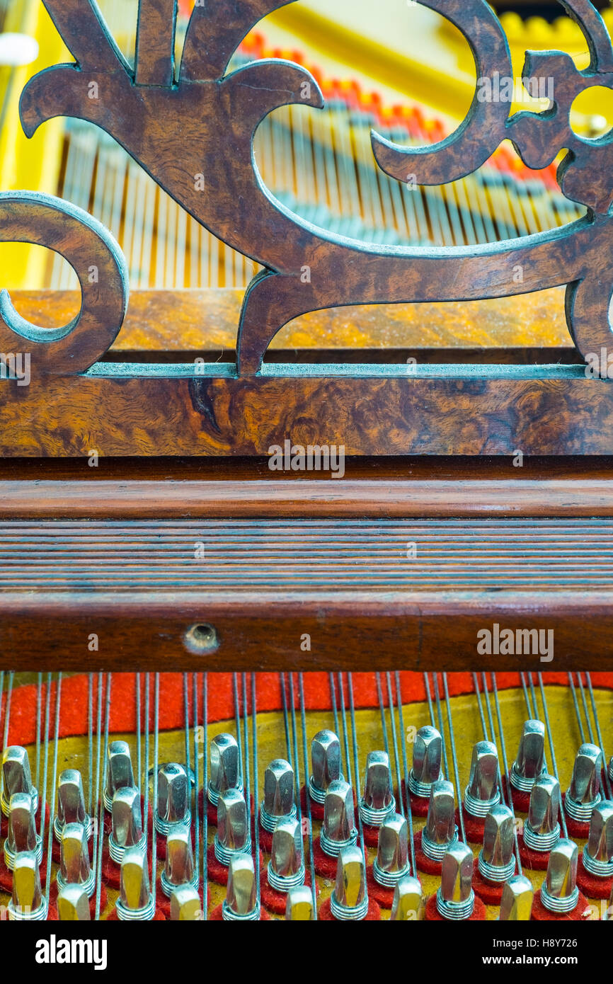 Close up of an antique grand piano showing the pins and strings. - Stock Image