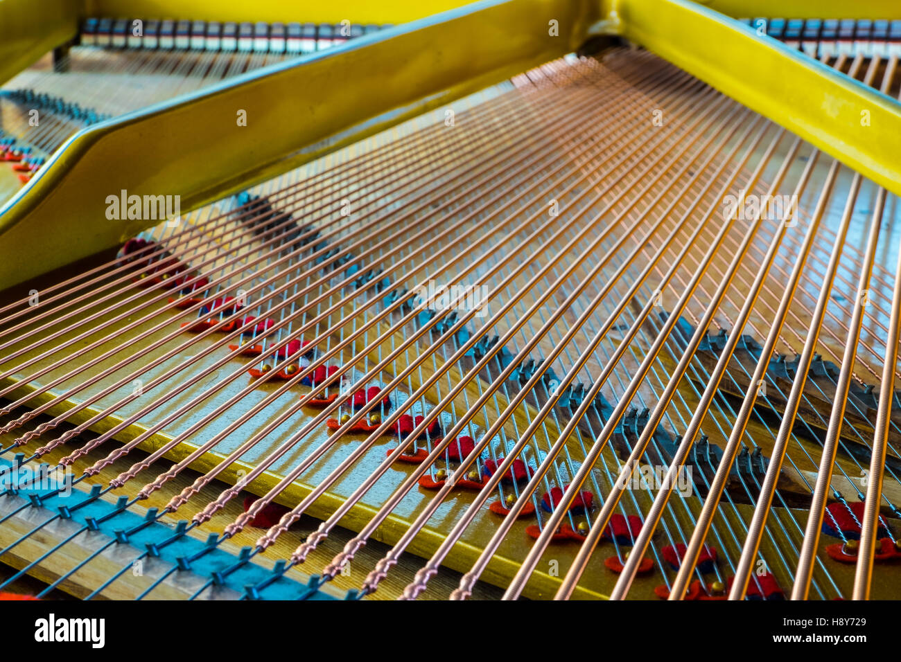 Close up of an antique grand piano showing the sounding board and strings. - Stock Image