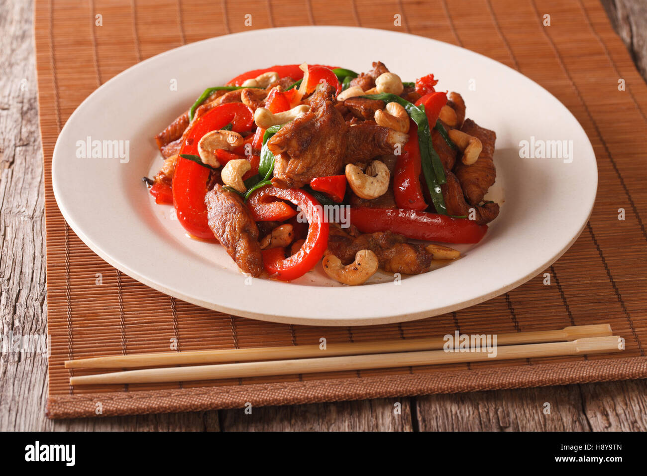 Thai Food: Fried chicken with vegetables and cashew nuts closeup on a plate on the table. horizontal - Stock Image
