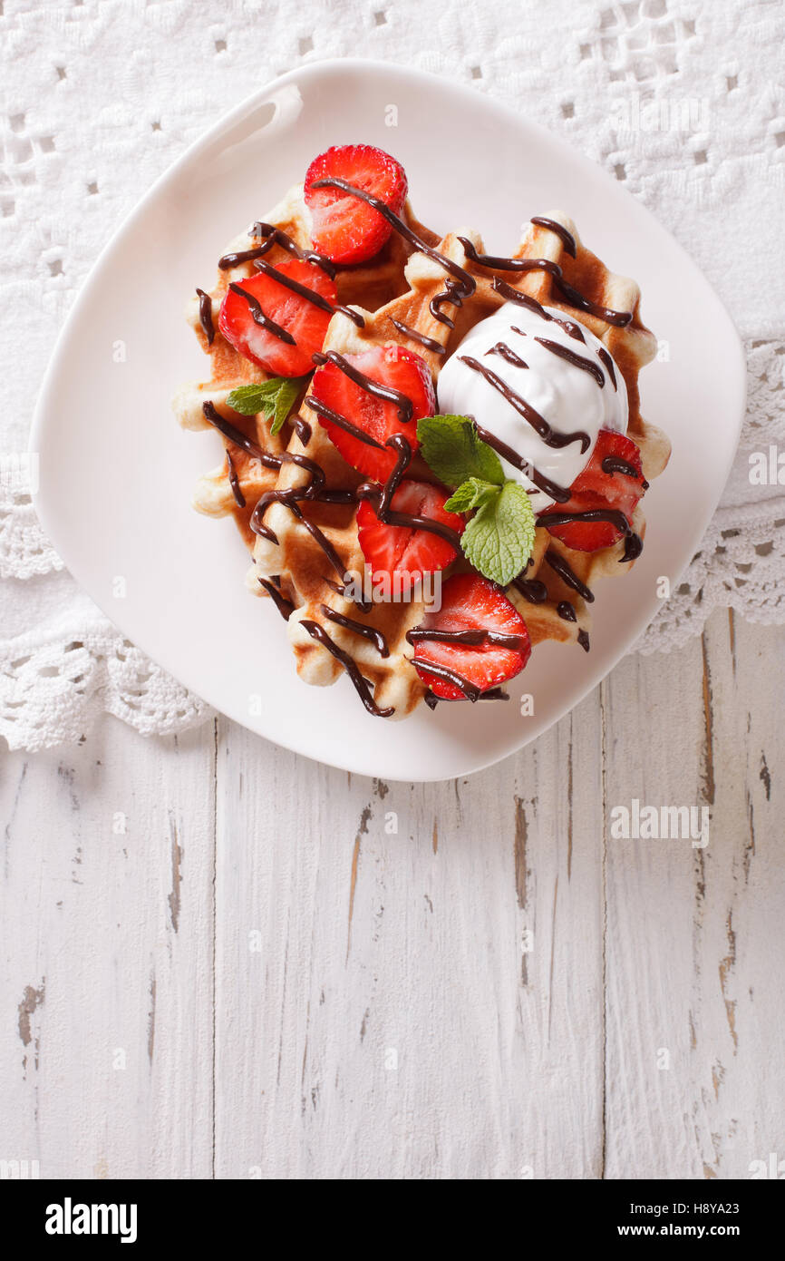 Tasty waffles with strawberries, whipped cream and chocolate frosting close up. Vertical view from above - Stock Image