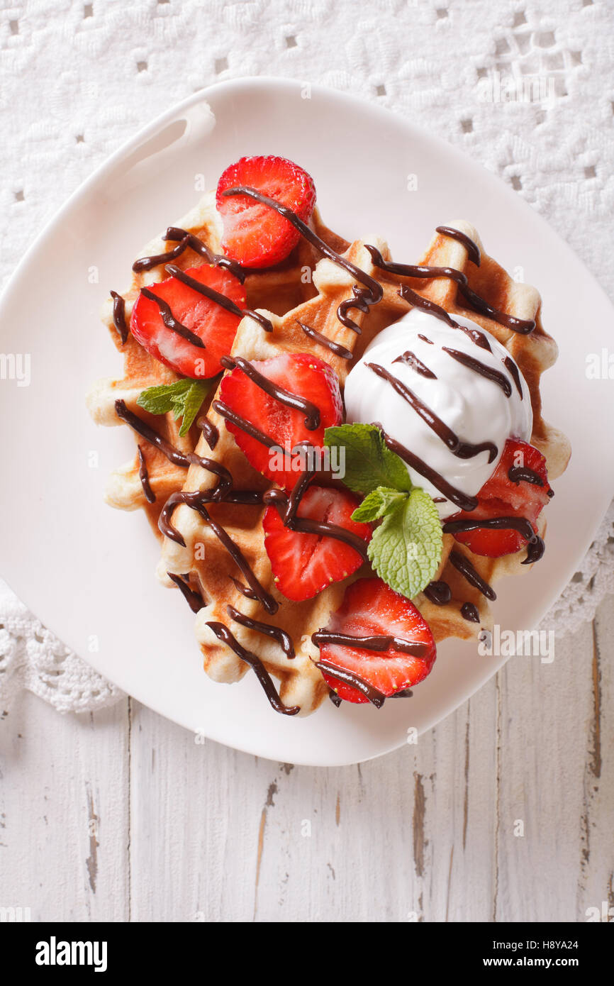 Belgian waffles with strawberries and chocolate topping on a plate. Vertical view from above - Stock Image