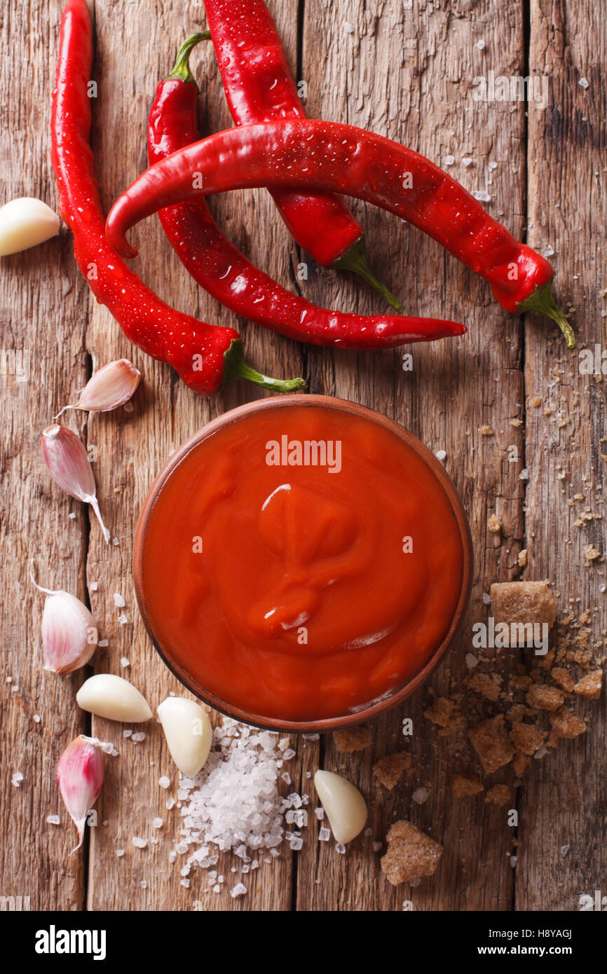 Freshly prepared Sriracha Hot chilli Sauce close-up on the table. vertical view from above - Stock Image