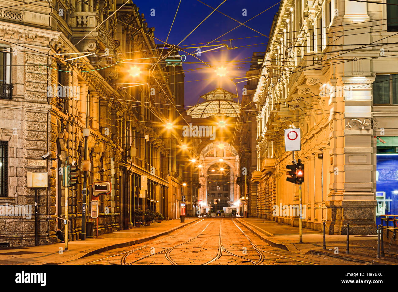 Milan pass-through street in historic downtown with tramway and wires at sunrise between baroque architecture houses - Stock Image