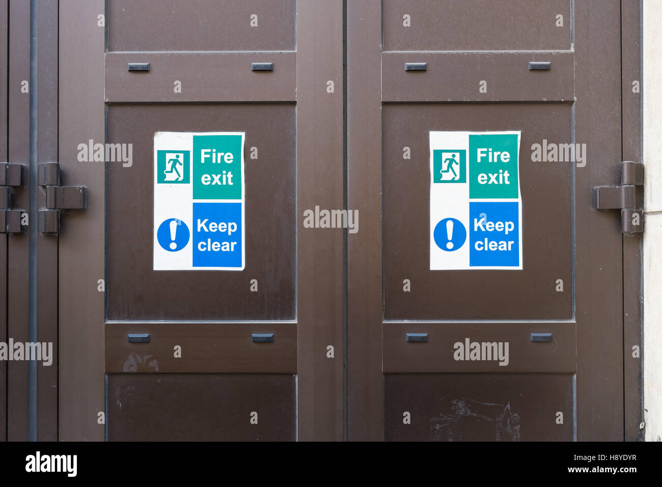 """Steel double doors with sign saying """"Fire exit, keep clear"""" Stock Photo"""