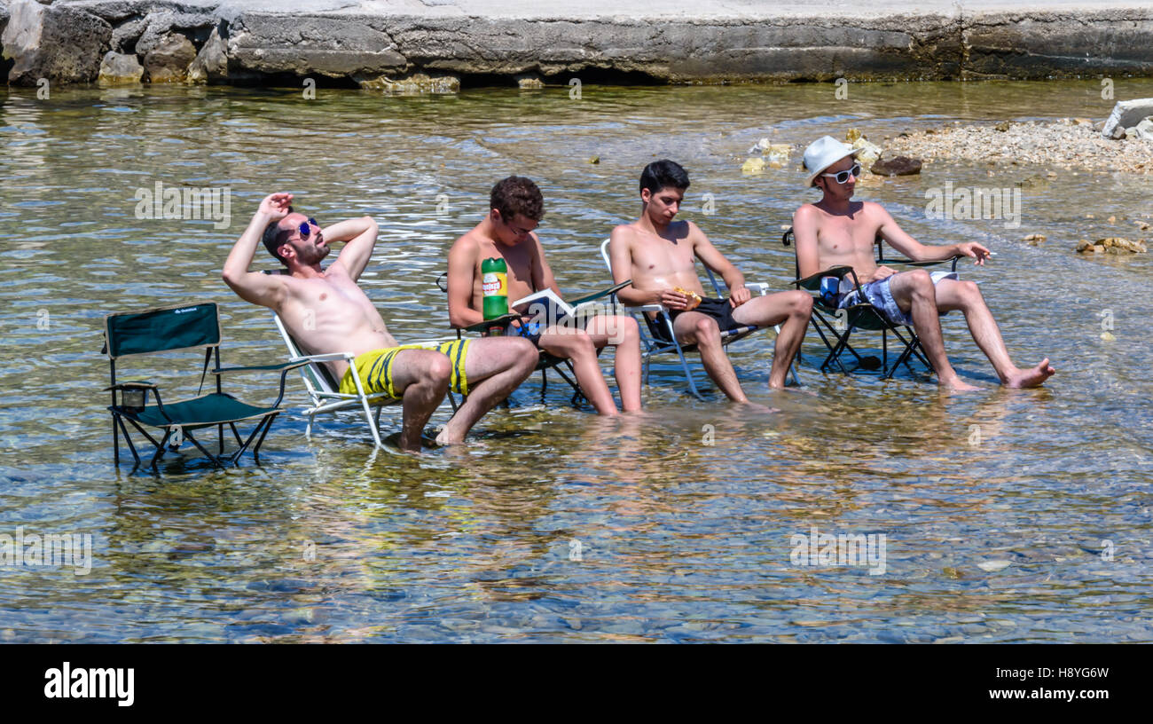 The boys sitting in the shallows on chairs Stock Photo