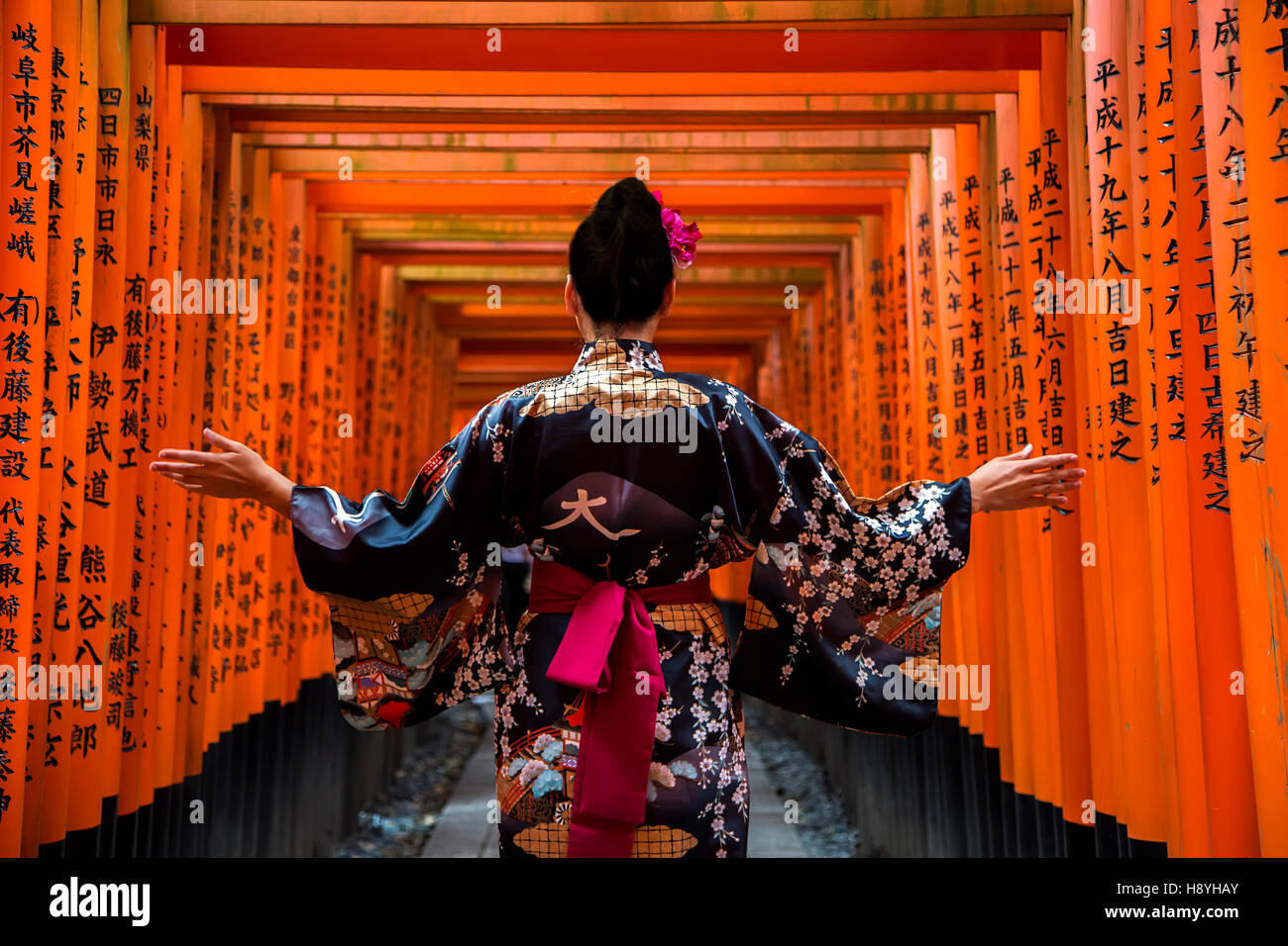 KYOTO, JAPAN - OCTOBER 8, 2016: Unidentified woman at walkway in Fushimi Inari shrine in Kyoto, Japan. This popular - Stock Image