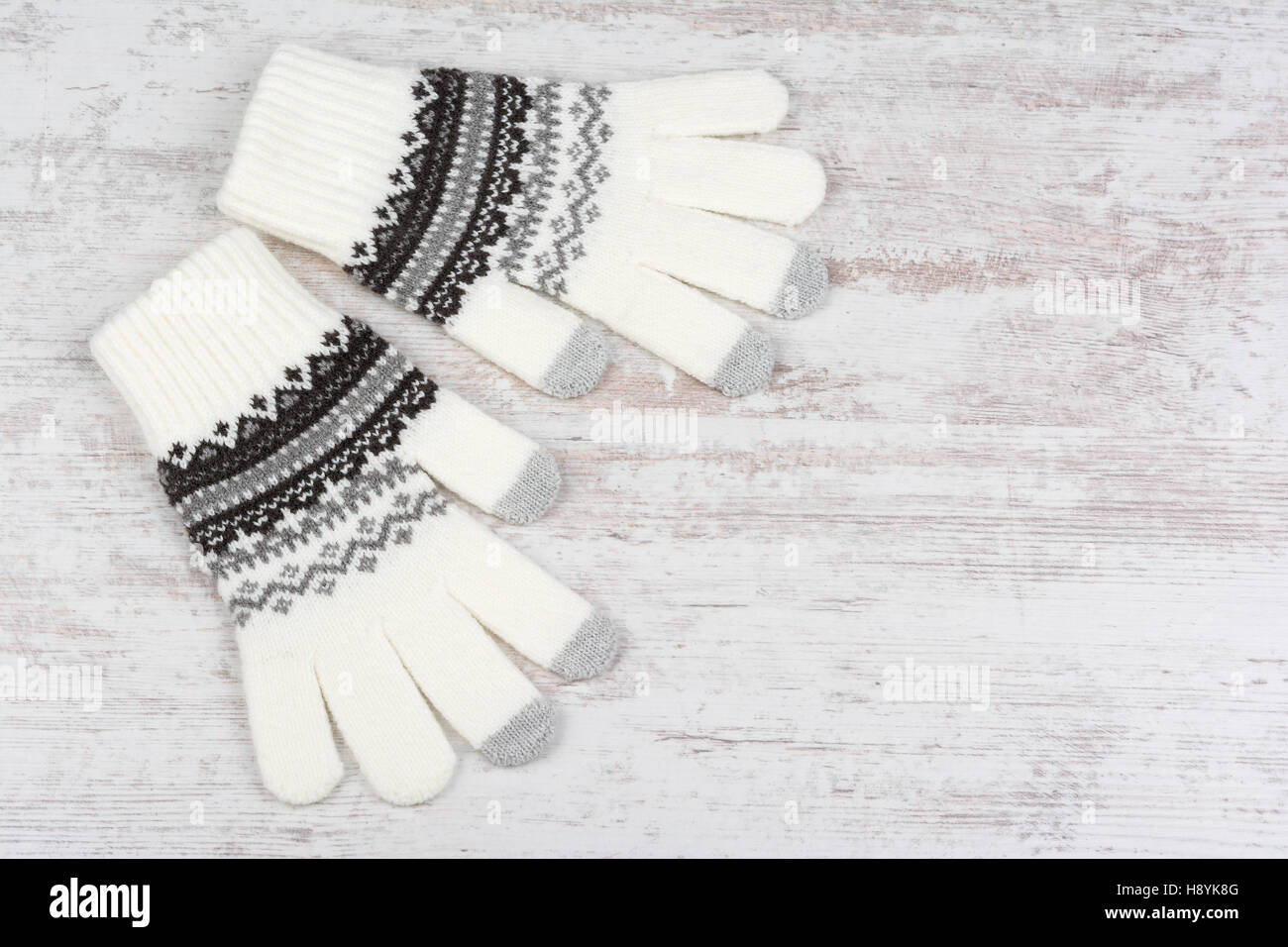 A pair of winter knitted gloves on white wooden background - Stock Image