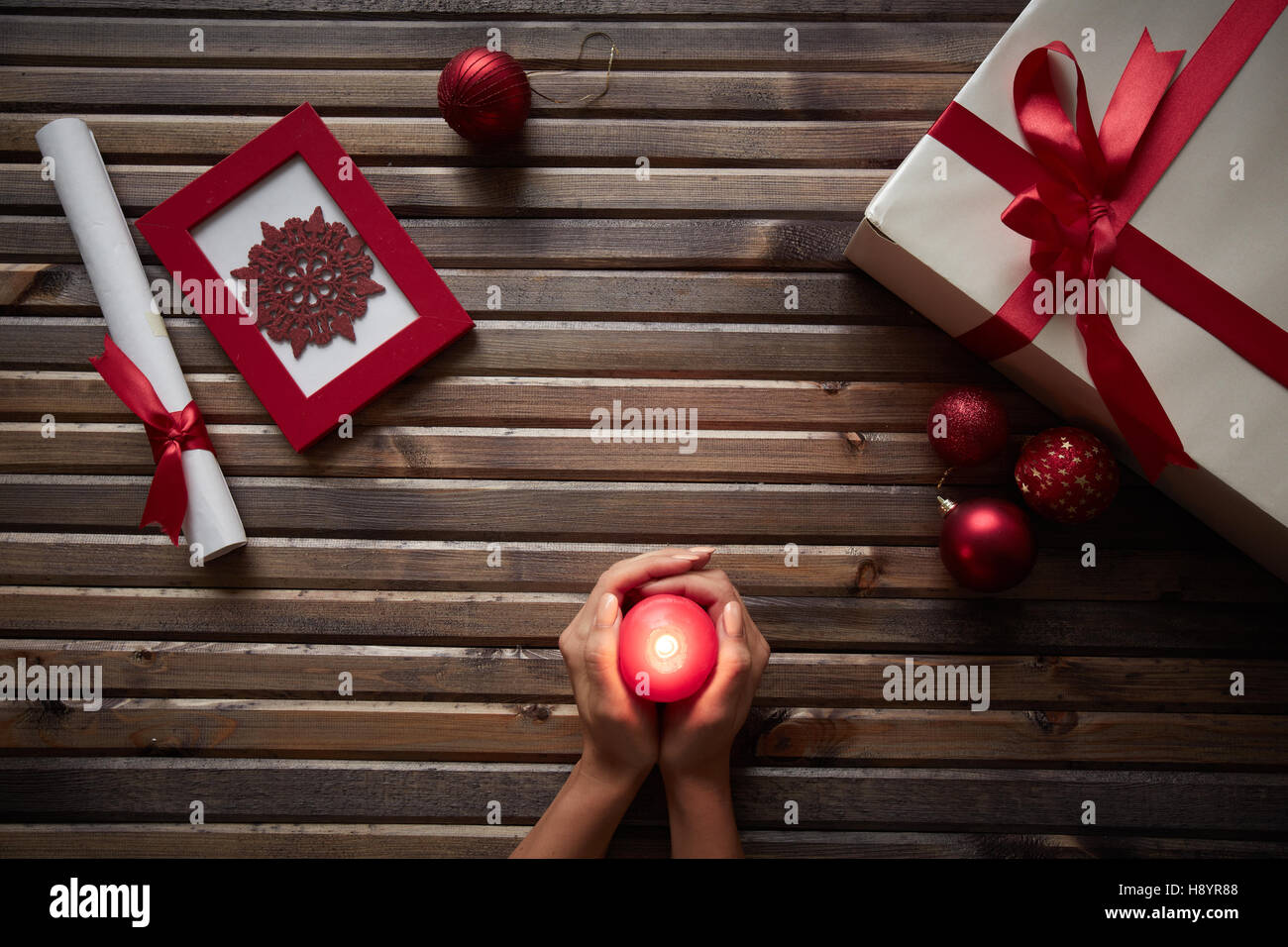 Human Hands Holding Red Burning Candle Being Surrounded By Xmas