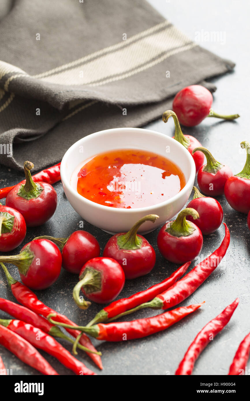 Red chili peppers and chili sauce on kitchen table. - Stock Image