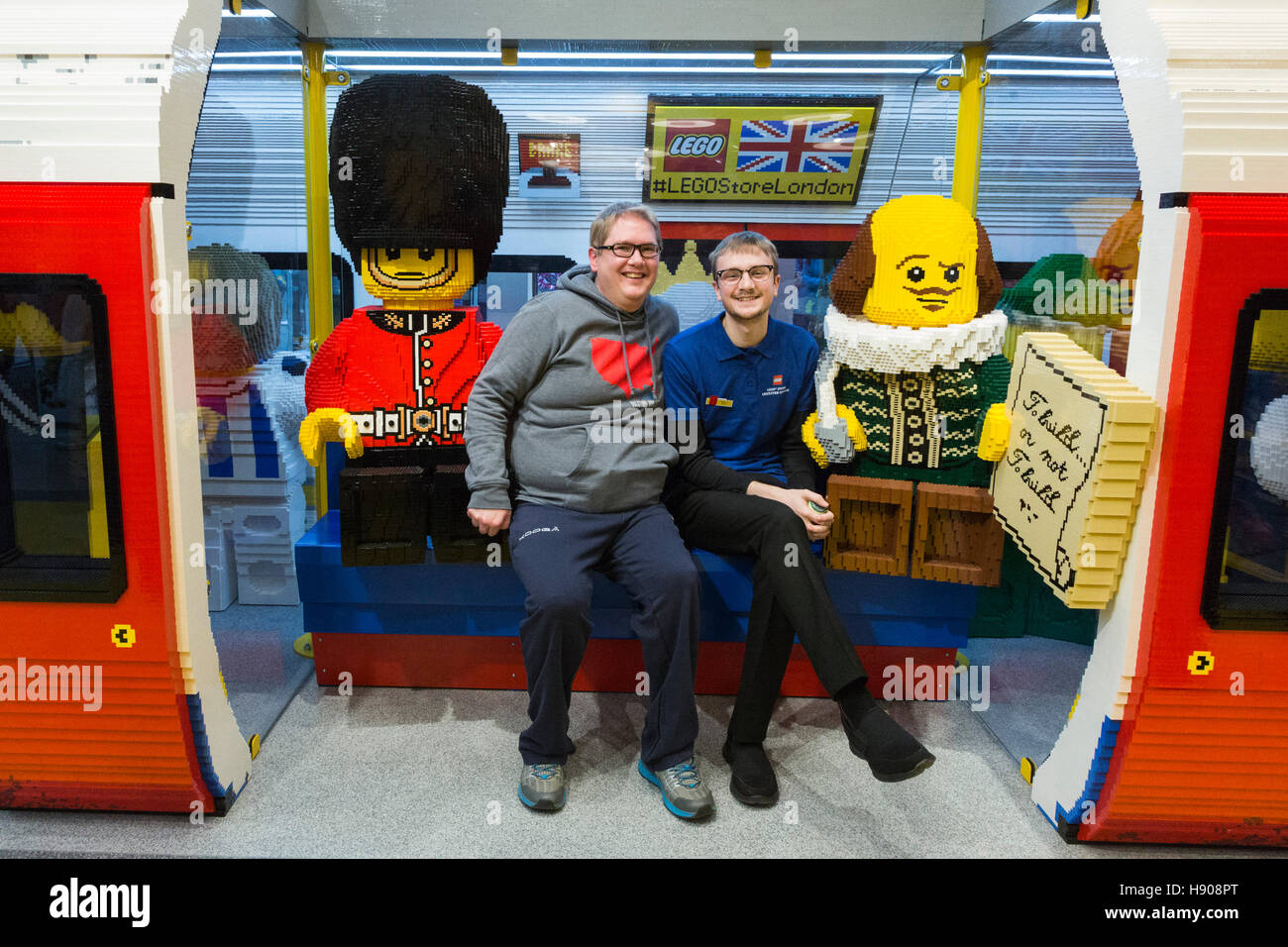 London, UK. 17 November 2016. A customer and a shop assistant take a seat in a tube train made of LEGO bricks. London's - Stock Image