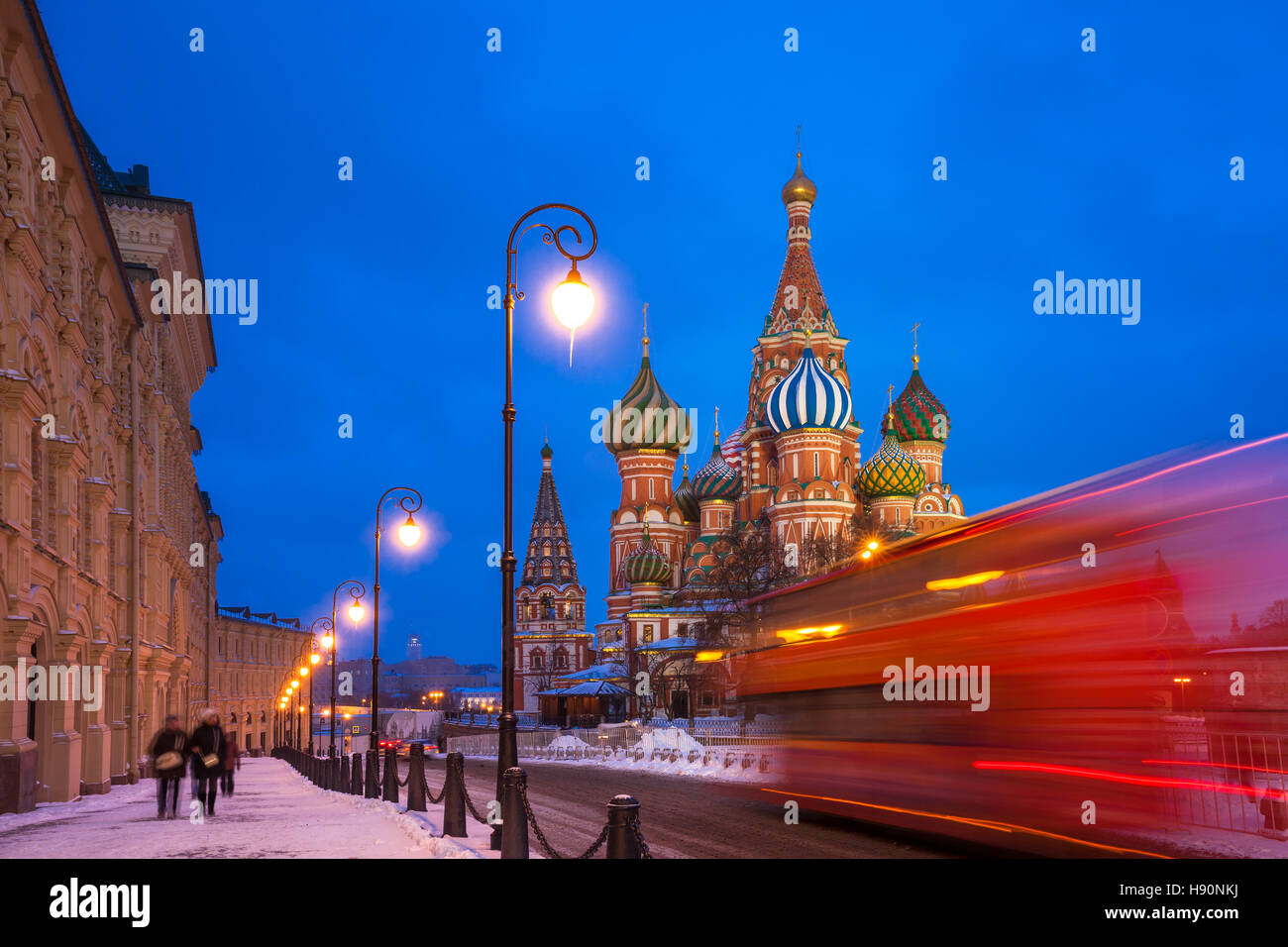 Red touristic bus passing by St. Basils Cathedral at dusk, Red Square, Moscow, Russia - Stock Image