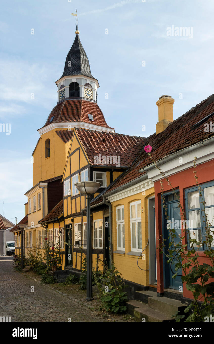 The old church bell tower of St Nicolas and colorful houses in the city of Faaborg, Denmark - Stock Image