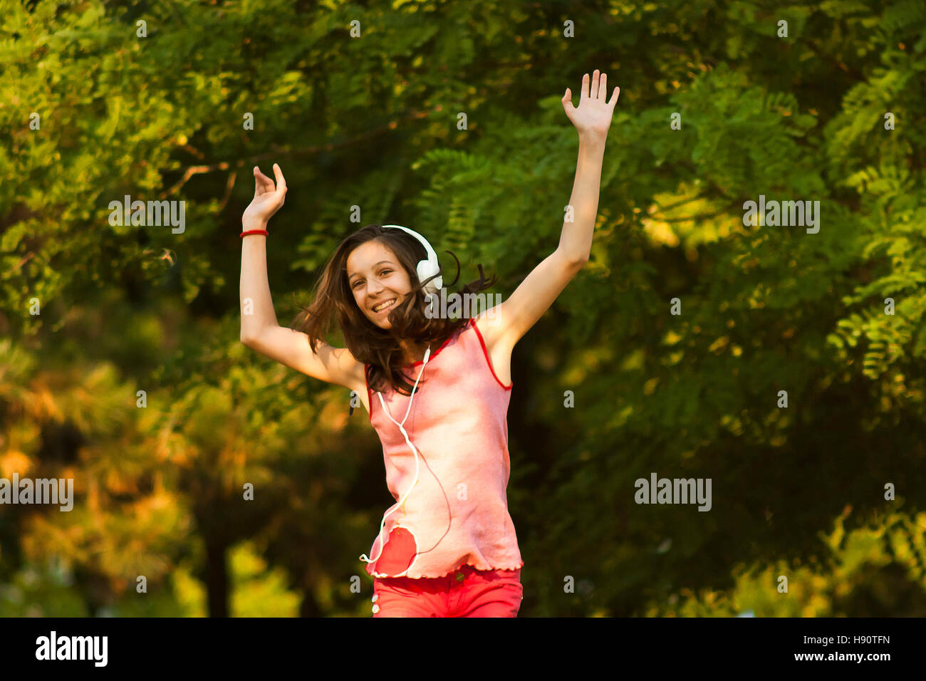 Happy teenage girl in red dancing in nature while listening to the music on headphones, smiling and looking at camera, - Stock Image