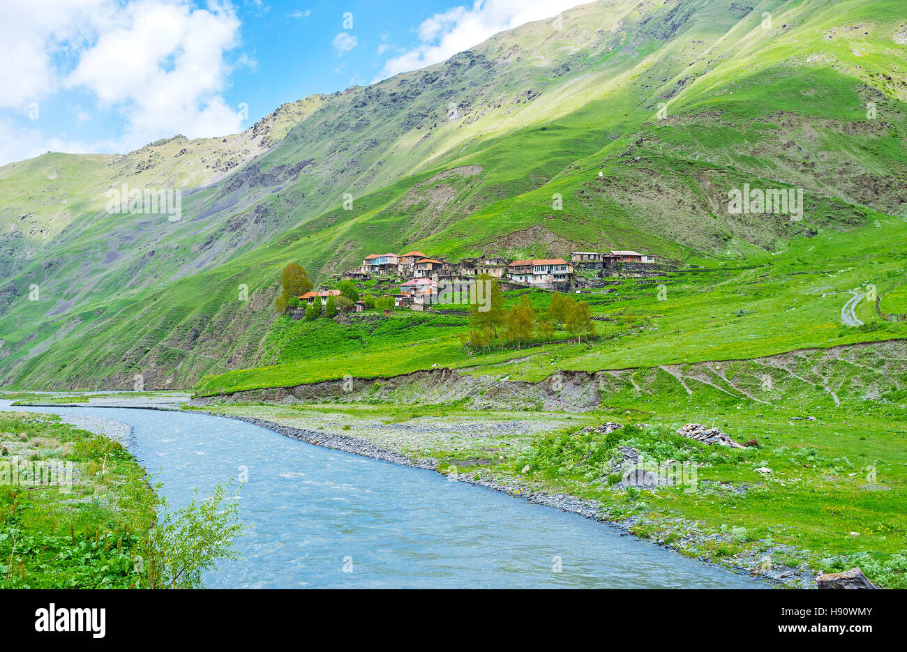 The colorful houses of Akhaltsikhe village on the green slope, by the Snostskali river, Sno Gorge, Georgia. - Stock Image