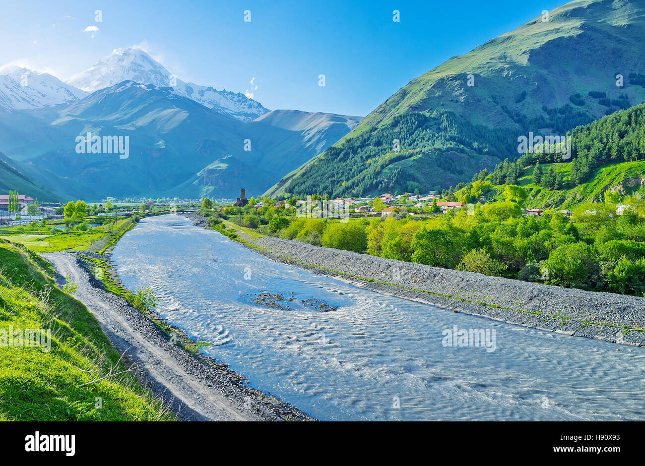The sunny weather in Sno valley offers the view on the Kazbek Mount, rising above the villages, Kazbegi, Georgia. - Stock Image