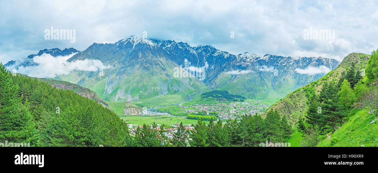 The view on Stepantsminda resort in the mountain valley above the spruces of Kazbegi National Park, Georgia. - Stock Image