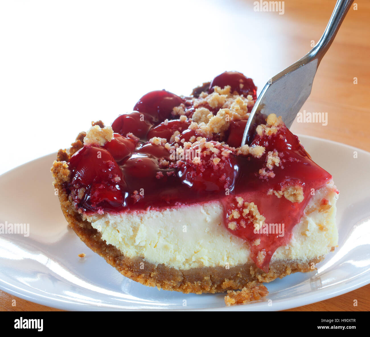 Fork going into a piece of cheesecake topped with cherries - Stock Image