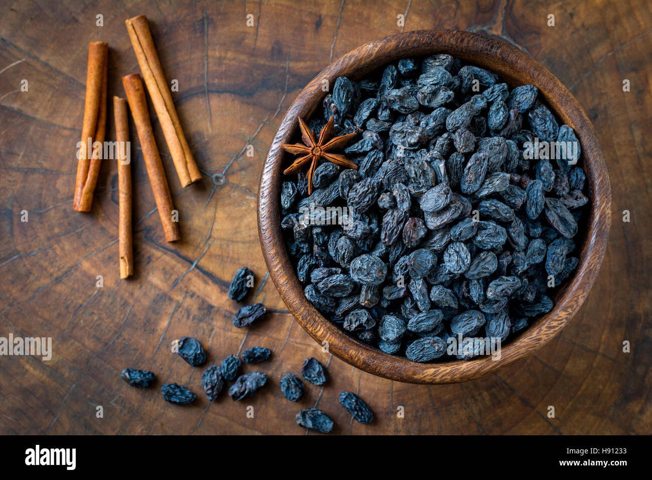 Black raisins and spices in wooden bowl. Top view, close up, horizontal - Stock Image