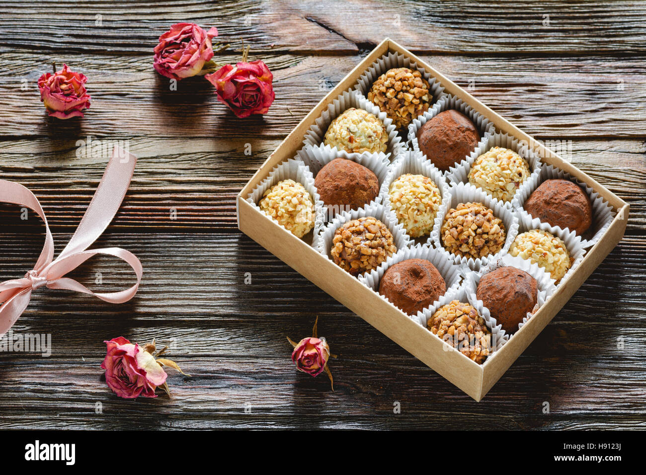 Box of delicious chocolates and pralines and dried pink roses. Valentine's day gift, Valentine day concept - Stock Image