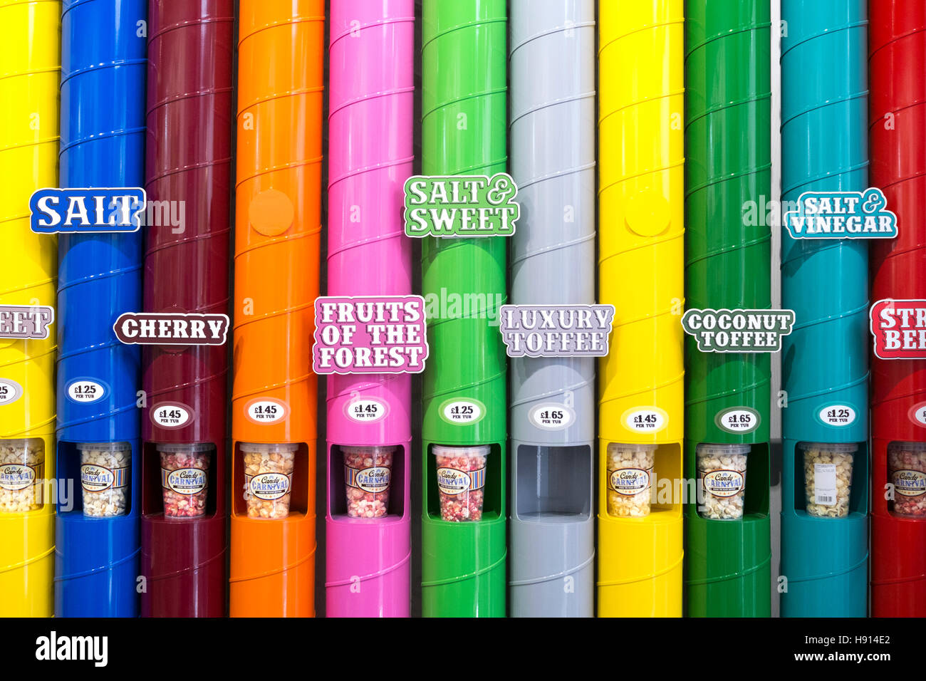 A display of varieties of popcorn flavours, SALT, CHERRY, SWEET, FRUITS, LUXURY TOFFEE, COCONUT, in coloured vertical - Stock Image