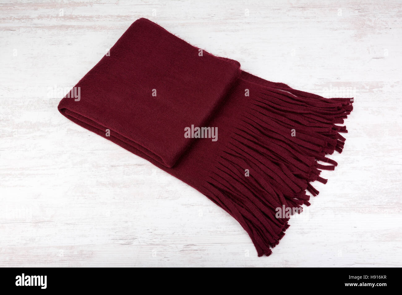 Woolen winter scarf on a white wooden background - Stock Image