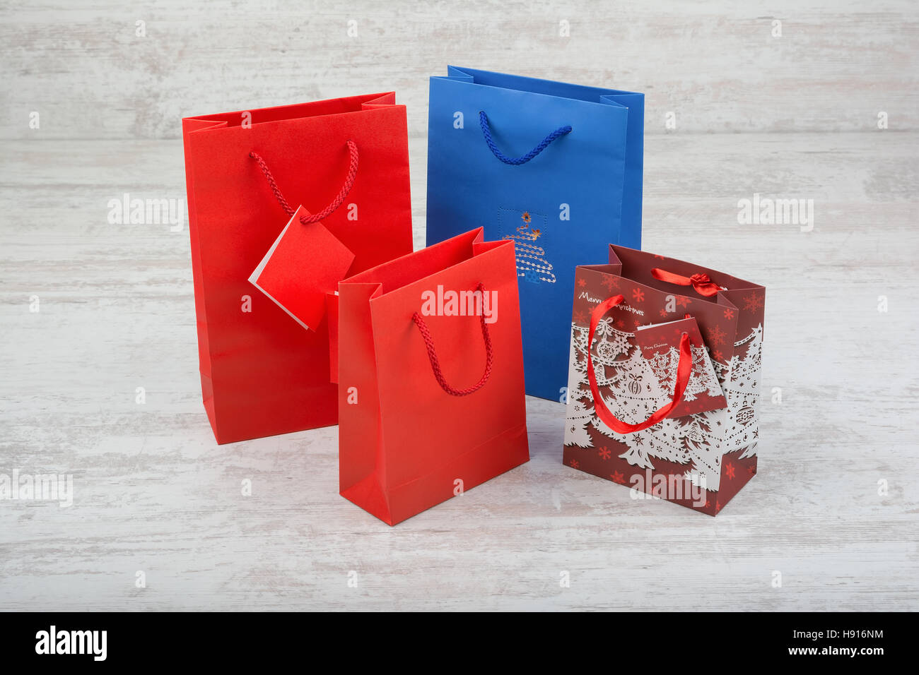 Red and blue gift bags on a white wooden background - Stock Image