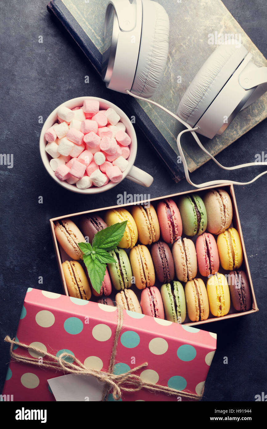 Colorful macaroons in a gift box and headphones on stone table. Sweet macarons. Top view. Toned - Stock Image