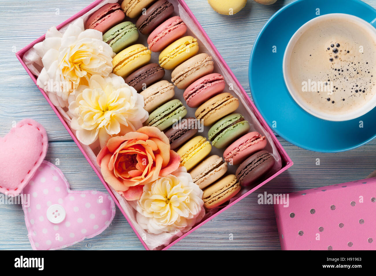 Colorful macaroons and coffee on wooden table. Sweet macarons in gift box and hearts. Top view - Stock Image