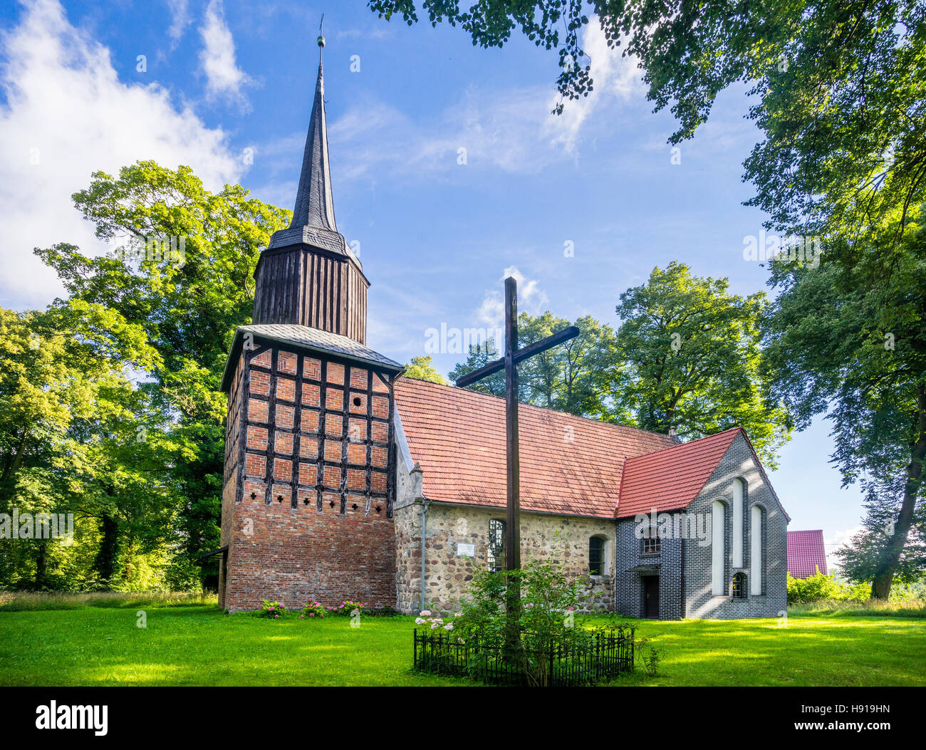 medieval village church of Ribokarty with half-timbered steeple toped by a barouque spire, West Pomerania, Poland - Stock Image