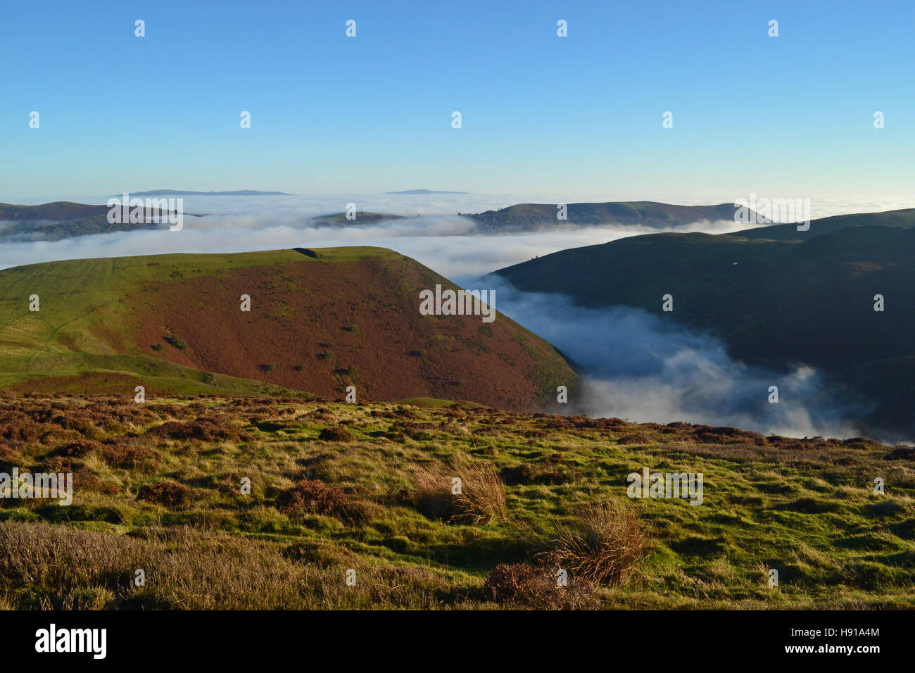 View from the Long Mynd, looking down over clouds in Carding Mill Valley, Church Stretton, Shropshire, UK Stock Photo