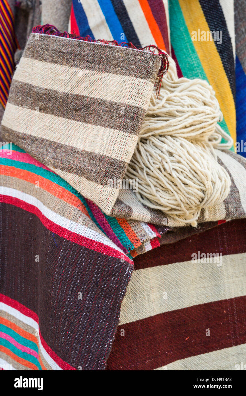 Rugs and carpets and bags displayed outside a shop in the souk, Essaouira, Morocco - Stock Image