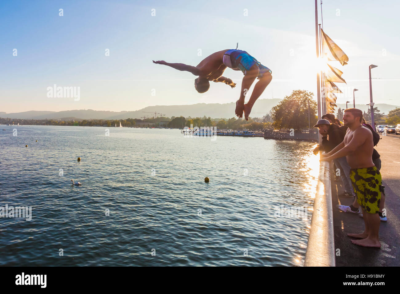 YOUNG MAN JUMPING FROM QUAIBRUCKE BRIDGE INTO LAKE ZURICH, ZURICH, SWITZERLAND - Stock Image