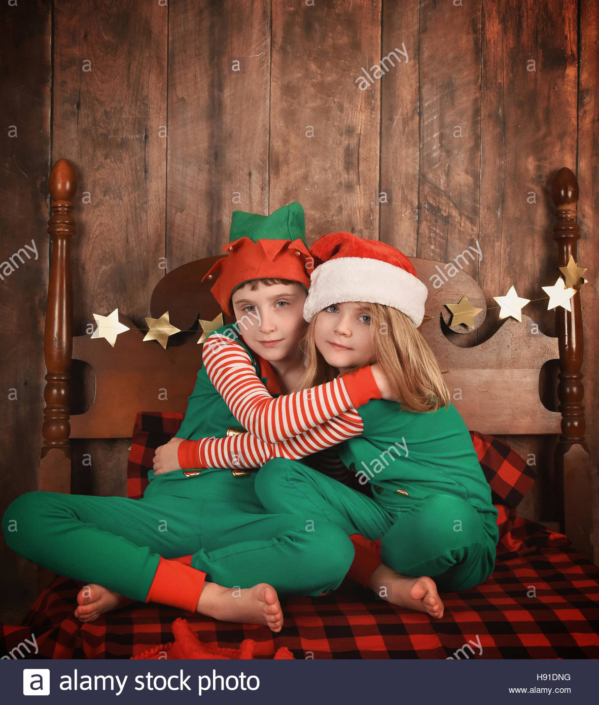 Little children wearing pajamas with Christmas hats hugging each other on a bed for a family at home concept or Stock Photo