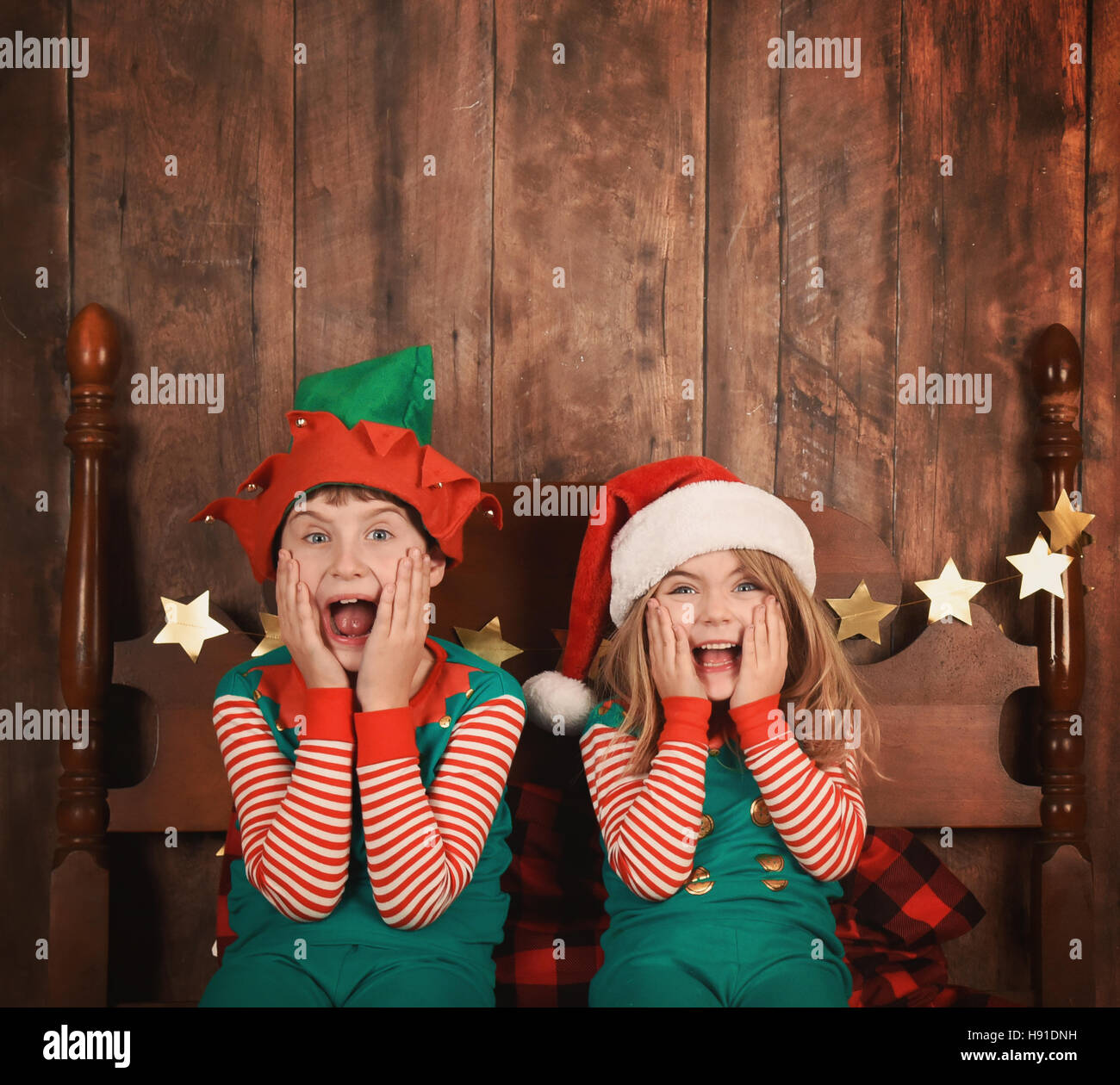 Two funny young children are surprised and excited sitting on a bed with Christmas pajamas with a wood wall. Use - Stock Image