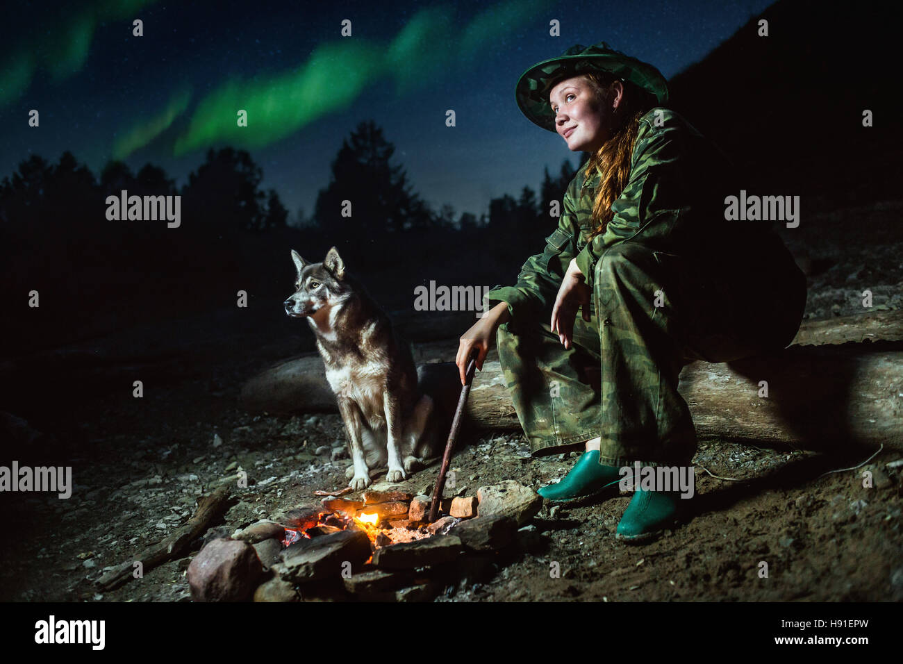 Scout girl with her dog around campfire at night  stars and aurora borealis - Stock Image