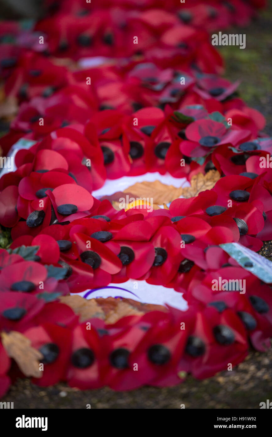 Poppy wreaths laid at the base of a war memorial - Stock Image