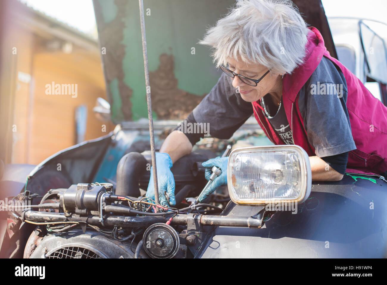 Elderly car mechanic working on her vintage car - Stock Image