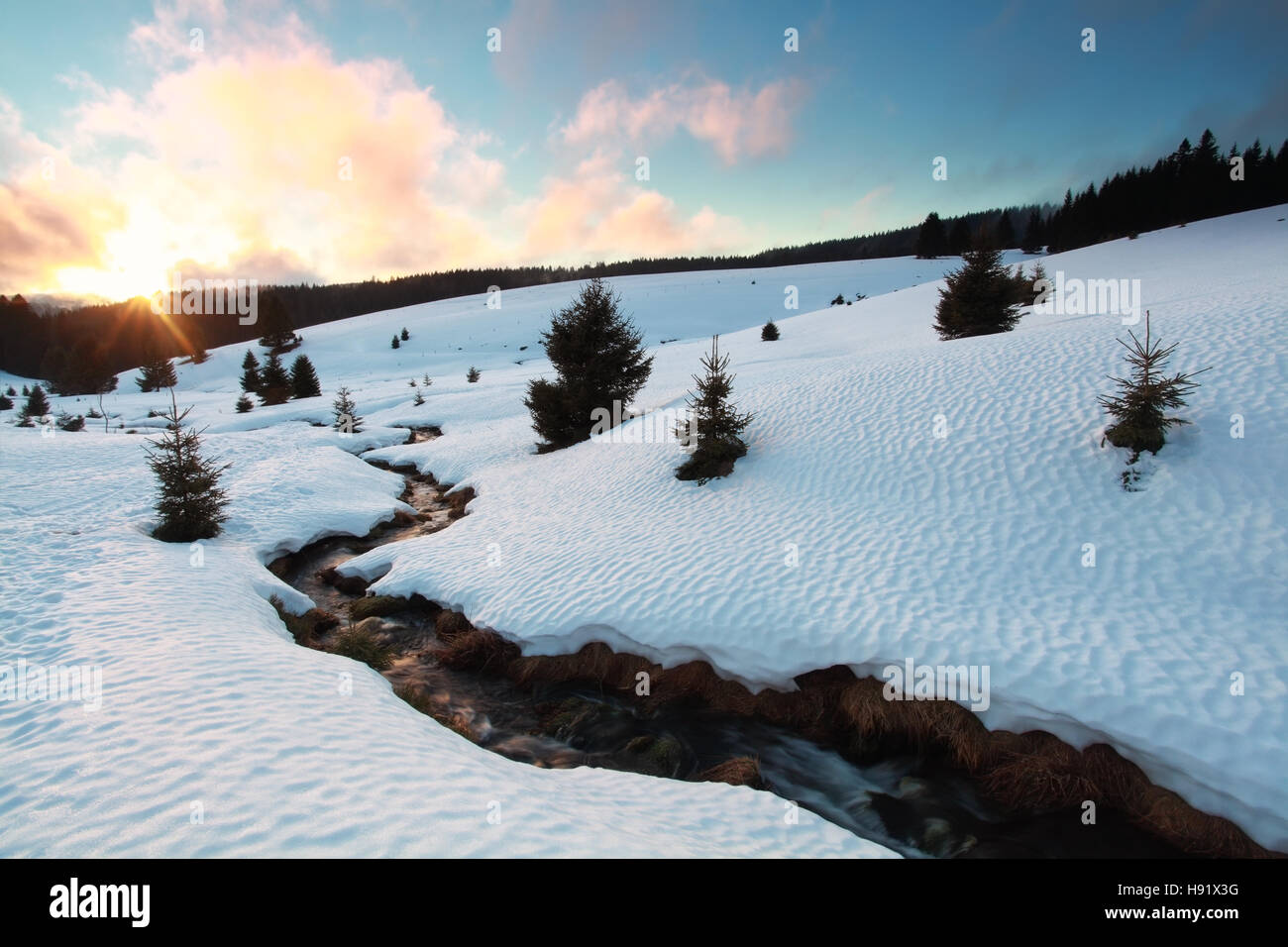 winter sunset over snow mountains with river, Germany - Stock Image
