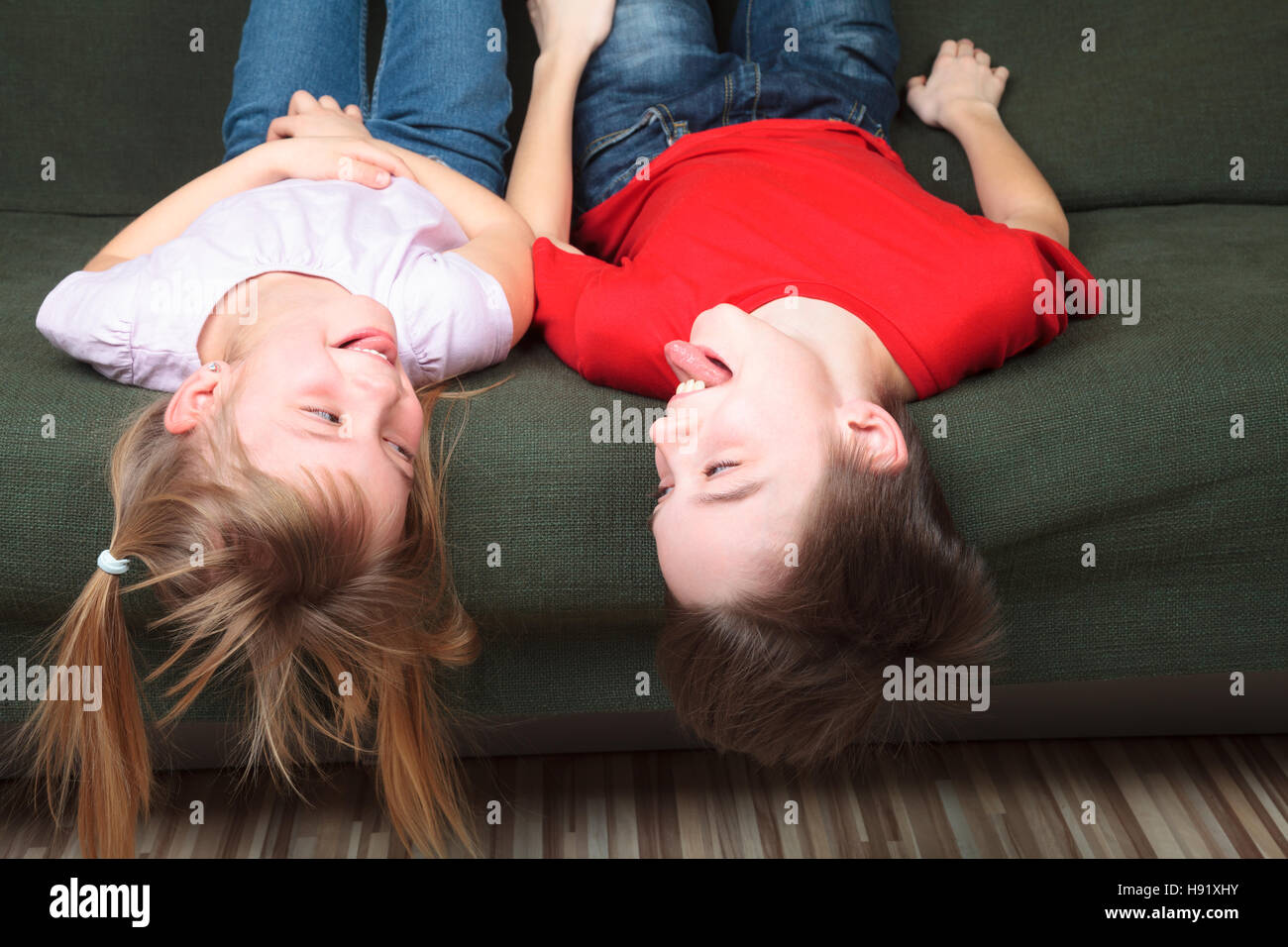 Brother and sister  wearing casual clothes  laying on a green sofa at home stick out tongues teasing each other - Stock Image